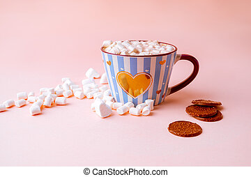 Hot chocolate drink with marshmallows and chocolate crisps in blue striped mug on pastel pink background