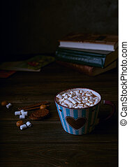 Hot chocolate drink with marshmallows in blue striped cup, stacked books on wooden rustic background