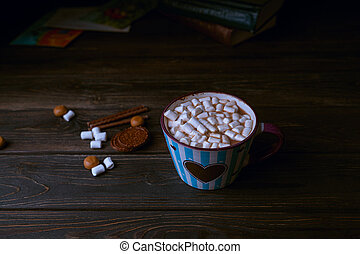 Hot chocolate drink with marshmallows in blue striped cup, stacked books on wooden rustic background, top view