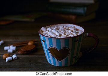 Hot chocolate drink with marshmallows in blue striped cup, stacked books on wooden rustic background. Closeup view