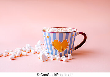 Hot chocolate drink with marshmallows in blue striped mug on pastel pink background