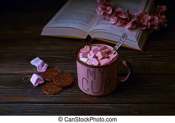 Hot chocolate drink with marshmallows in pink cup, open book on wooden rustic background