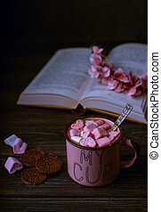 Hot chocolate drink with marshmallows in pink cup, open book on wooden rustic background, vintage mood