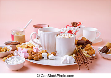 Hot chocolate in mugs, marshmallows, chocolates and cookies on pink background