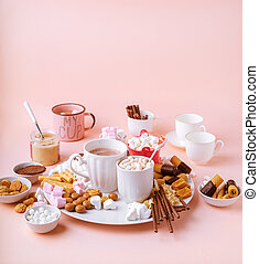 Hot chocolate in mugs, sweets assortment of marshmallows, chocolates and cookies on pink background