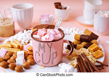 Hot chocolate in pink mug, sweets assortment of marshmallows, caramels, chocolates and cookies on pink background