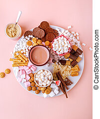 Hot chocolate, marshmallows, chocolates and cookies charcuterie board on pink background