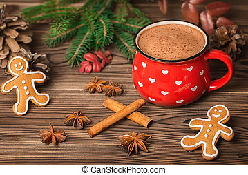 hot chocolate or cocoa, gingerbread cookies decorated, Christmas tree branch, cones, cinnamon and anis on wooden background, greeting card