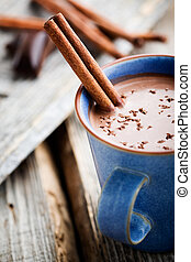 Hot chocolate with cinnamon stick in blue cup