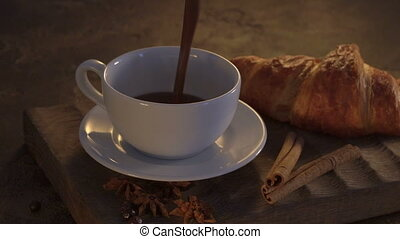 Hot chocolate with croissants and cinnamon sticks on grunge table