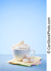 hot chocolate with marshmallows and cream on blue background