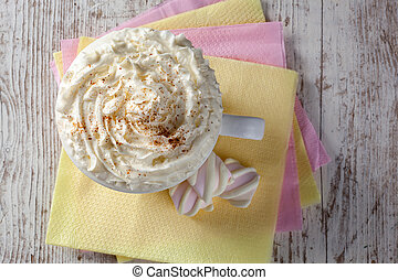 hot chocolate with marshmallows and cream on wooden background