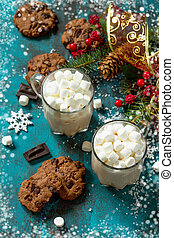 Hot Chocolate with Marshmallows and Homemade Chocolate Chip Cookies on a blue stone or concrete table.