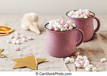 Hot chocolate with marshmallows in mugs on a linen tablecloth with a Christmas toy. High quality photo