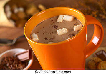 Hot chocolate with marshmallows in orange cup surrounded by ...