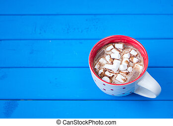 Hot chocolate with marshmallows isolated on blue wooden background.
