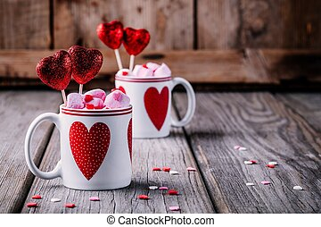 Hot chocolate with pink marshmallow in mugs with hearts for Valentine's day