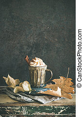 Hot chocolate with whipped cream and cinnamon on table