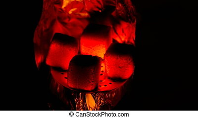 Hot coals in the hookah bowl in darkness closeup. Time lapse video.