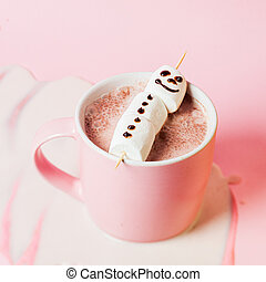Hot cocoa with marshmallow snowman in a pink mug on a pink background