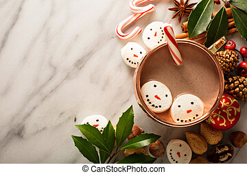 Hot cocoa with marshmallow snowmen and candy cane