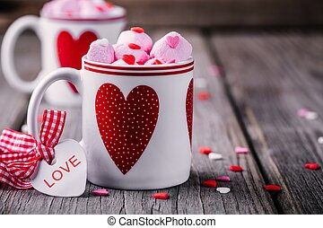 Hot cocoa with pink marshmallow in mugs with hearts for Valentine's day