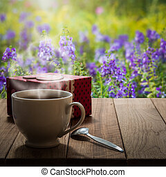 Hot coffee and gift box on wooden table in the meadow