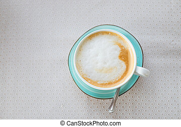 Hot coffee cappuccino latte art in jade color cup isolated on beige table.Cappuccino coffee cup top view.Latte art on milky foam.Hot Italian energizing beverage served in green ceramic mug