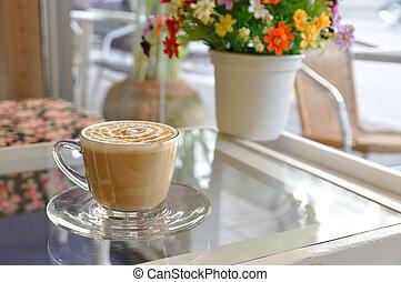 Hot coffee caramel macchiato on glass table be side beautiful flowers pot.