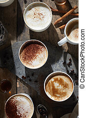 Hot coffee cup and coffee beans on wooden table.