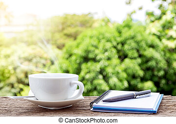 Hot coffee cup with a notebook and a pen
