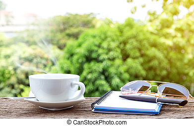 Hot coffee cup with a notebook, sunglasses and pen.