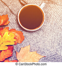 Hot Coffee cup with autumn leaves over wooden background. Abstract autumn image