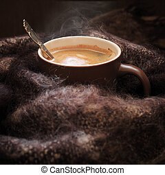 Hot coffee in warm scarf