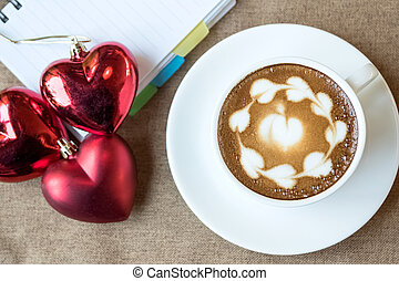 Hot coffee latte, latte art with red heart in white cup on a table