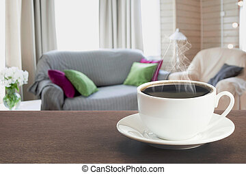 Hot coffee on tabletop in modern living room with chair, soft divan.