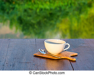 Hot coffee on wooden saucer and on wooden table