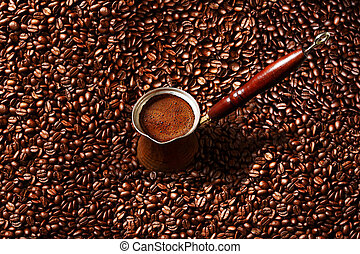 Hot coffee prepared in a Turk. Top view on beautiful foam with coffee beans background.