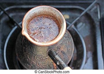 Hot coffee prepared in turk on gas. Closeup.