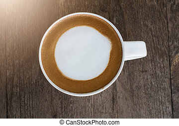 hot coffee with foam milk on wooden background.