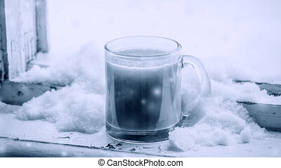 Hot coffee with milk in glass mug, which is studded with snow on windowsill on window in winter. During snowfall. Cinemagraph seamless loop animation motion gif render background. White blue color