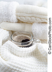 Hot coffee wrapped in a white woolen scarf