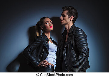 man looking down on sexy woman in leather jacket