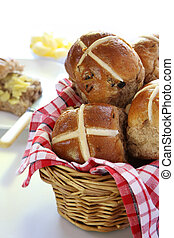 Basket of hot cross buns, with one cut and buttered in the background. Easter symbol.