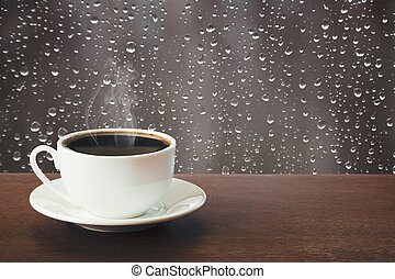Hot cup of black coffee in a rainy day on tabletop.