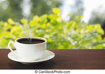 Hot cup of black coffee in a sunny day on tabletop. Summer. Outdoors.