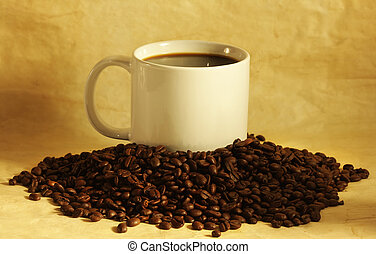 Hot cup of coffee on a pile of coffee beans