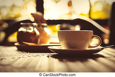 hot cup of coffee on the wood table near the in the morning.