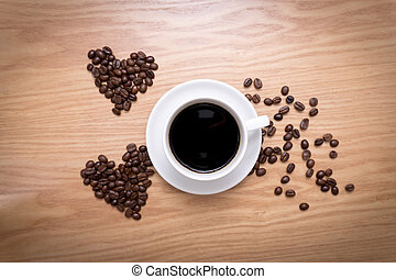 Hot cup of espresso and heart shape made from coffee beans on wooden surface.