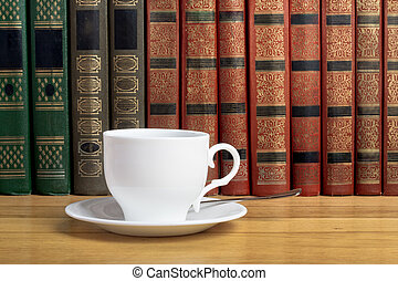 Hot cup of fresh coffee on the wooden table and a stack of books